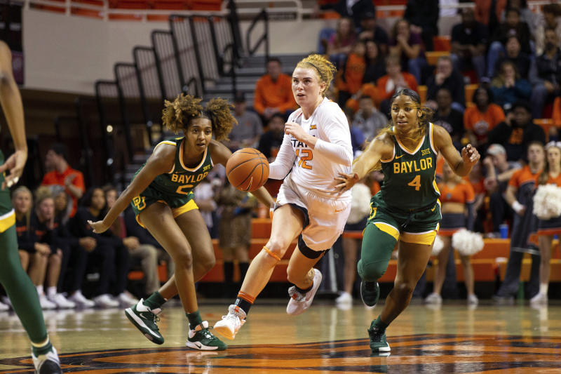 Oklahoma State forward Vivian Gray (12) drives the ball past Baylor guard DiDi Richards (2) and Baylor guard Te'a Cooper (4) during the first half of an NCAA college basketball game in Stillwater, Okla., Saturday, Feb. 15, 2020. (AP Photo/Brody Schmidt)