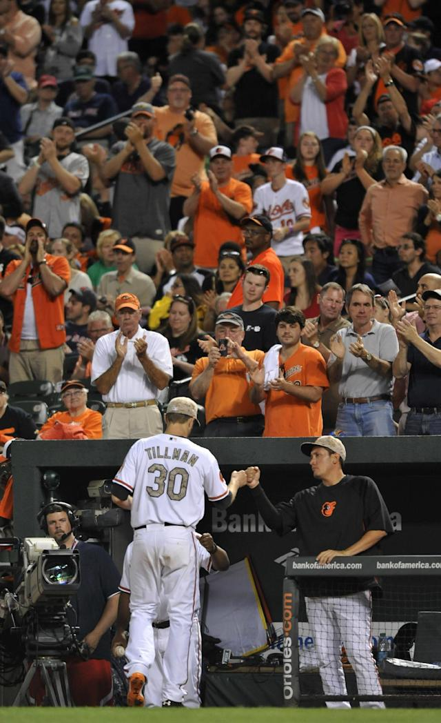 Baltimore Orioles pitcher Chris Tillman is congratulated by Freddie Garcia as he leaves the game with a standing ovation against the Boston Red Sox in the seventh inning of a baseball game, Friday, June 14, 2013, in Baltimore. The Orioles won 2-0. (AP Photo/Gail Burton)