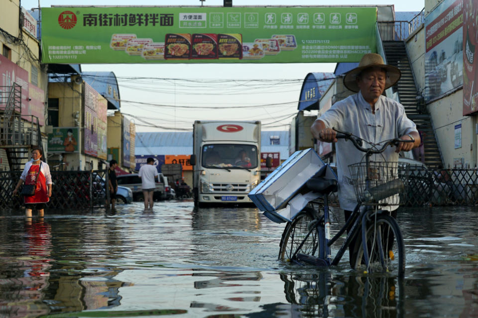 A man carries goods on his bicycle as he walks out of the the Yubei Agricultural and Aquatic Products World in Xinxiang in central China's Henan Province, Monday, July 26, 2021. Record rain in Xinxiang last week left the produce and seafood market soaked in water. Dozens of people died in the floods that immersed large swaths of central China's Henan province in water. (AP Photo/Dake Kang)