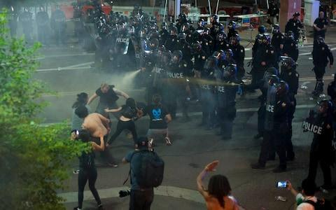 <span>Police use tear gas to break up protesters gathered outside of the Phoenix</span> <span>Credit: AFP </span>
