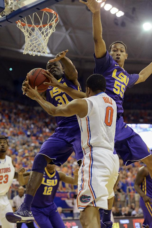 LSU forward John Odo (31) and LSU guard Tim Quarterman (55) go up to block a shot by Florida's Kasey Hill during the first half of an NCAA college basketball game on Saturday, March 1, 2014, in Gainesville, Fla. (AP Photo/Phil Sandlin)