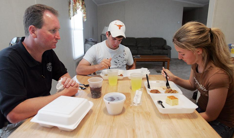 CHALMETTE, LA - MAY 11:  Cabrini High School junior Danielle DiMaggio (R) eats a box dinner with boyfriend Ben Navo (C) and her father David in the temporary trailer where she currently lives in May 11, 2006 in Chalmette, Louisiana. DiMaggio's house was heavily damaged by Hurricane Katrina and she currently lives in a trailer with her father while her mother and brother are still displaced in Lafayette, Louisiana. DiMaggio and every girl at Cabrini High School will be wearing dresses donated by 18-year-old Marissa West from Beltville, Maryland to their prom May 12th. (Photo by Mario Tama/Getty Images)