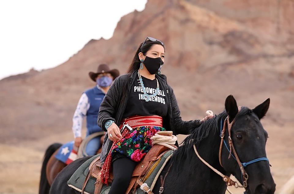 Allie Young, a Diné woman on the Navajo Nation in Arizona, is among a group of Native Americans as they ride on horseback to the polls on Election Day in Kayenta, Ariz., Tuesday, Nov. 3, 2020. (Larry Price via AP)