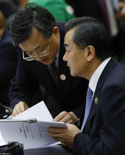 China's Foreign Minister Wang Yi, right, talks with an unidentified delegation member as he attends the 3rd East Asia Summit (EAS) Foreign Ministers' Meeting in Bandar Seri Begawan, Brunei, Tuesday, July 2, 2013. (AP Photo/Vincent Thian)