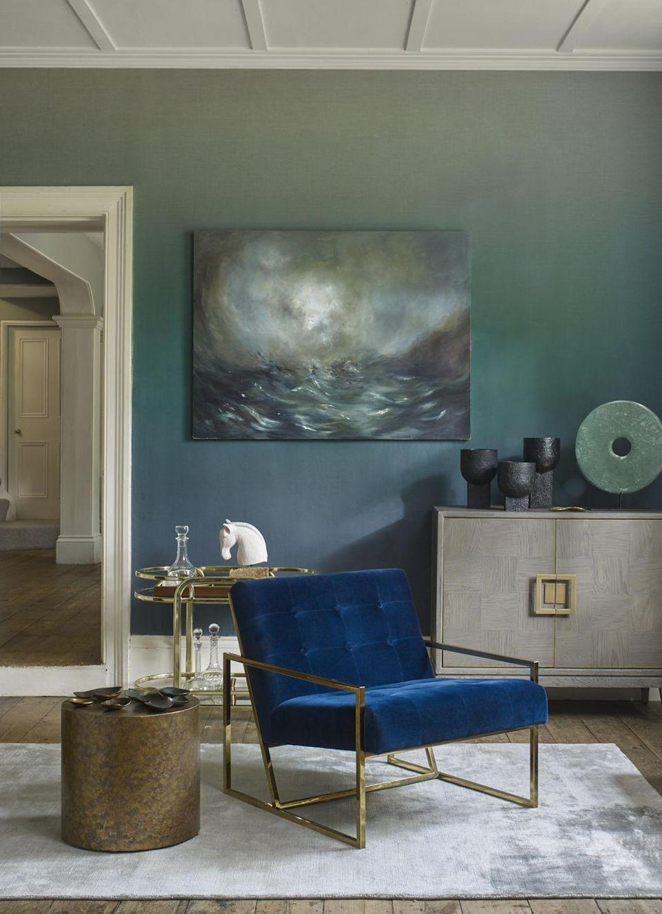"""<p>A lovely way to add colour to a plain living room is with <a href=""""https://www.housebeautiful.com/uk/decorate/walls/how-to/a461/how-to-paint-an-ombre-wall/"""" rel=""""nofollow noopener"""" target=""""_blank"""" data-ylk=""""slk:ombre"""" class=""""link rapid-noclick-resp"""">ombre</a> wallpaper. Choose your favourite shade then have a wall that begins with a deep tone at the bottom and graduates to a paler shade at the top. It's subtle, calming, and easy to live with, especially in this lovely blue.</p><p>Pictured: Horizon Deep Blue wallpaper, <a href=""""https://elizabethockford.com/horizon/"""" rel=""""nofollow noopener"""" target=""""_blank"""" data-ylk=""""slk:Elizabeth Ockford"""" class=""""link rapid-noclick-resp"""">Elizabeth Ockford</a></p>"""