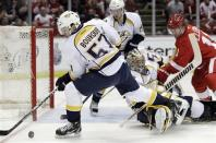 Nashville Predators left wing Gabriel Bourque (57) controls the puck after a deflection by goalie Pekka Rinne during the first period of Game 3 of an NHL hockey Stanley Cup first-round playoff series in Detroit, Sunday, April 15, 2012. (AP Photo/Carlos Osorio)