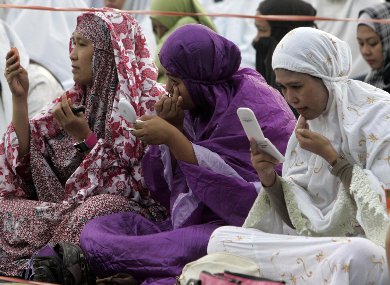 Filipino Muslim women fix themselves before the start of a morning prayer celebrating Eid al-Fitr, a Muslim holiday marking the end of Ramadan, the Islamic holy month of fasting, at the Quirino grandstand in Manila, Philippines, Tuesday, Aug. 30, 2011. (AP PHoto/Pat Roque)