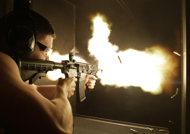 """FILE - In this Thursday, Aug. 28, 2014, file photo, Simon Winson of Manchester, England fires a fully automatic machine gun at Machine Guns Vegas in Las Vegas. Strict gun laws keep the real guns out of reach for most people, especially outside the U.S., indoor shooting ranges with high-powered weapons have become a hot tourist attraction. A gun control lobbying organization is adding Nevada to efforts to show gun rights groups including the National Rifle Association are behind a """"Second Amendment sanctuary"""" drive in several Western U.S. states. (AP Photo/John Locher, File)"""