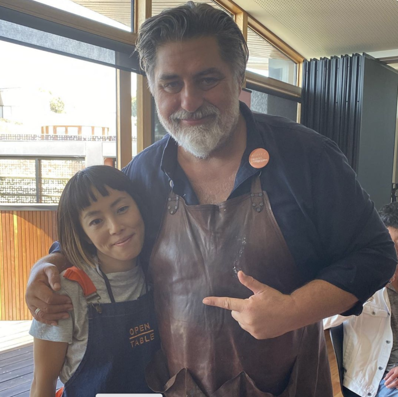 A photo of Matt Preston wearing a blue shirt and leather apron with a woman from Open Table.