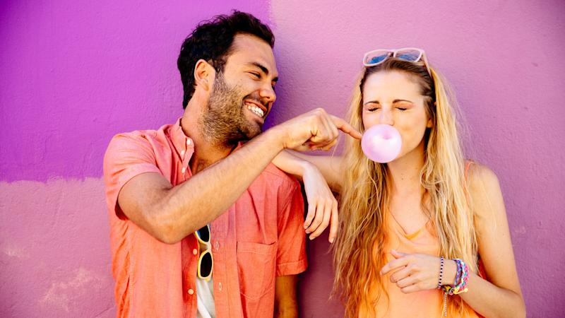 Happy playful young couple against pink background.