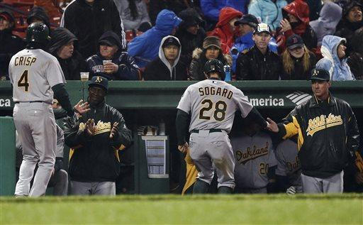 Oakland Athletics' Coco Crisp (4) and Eric Sogard (28) are greeted at the dugout after scoring on a two-run single by John Jaso during the fifth inning of a baseball game against the Boston Red Sox at Fenway Park in Boston, Tuesday, April 23, 2013. (AP Photo/Winslow Townson)