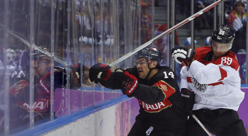 Austria forward Raphael Herburger checks Canada forward Chris Kunitz in the second period of a men's ice hockey game at the 2014 Winter Olympics, Friday, Feb. 14, 2014, in Sochi, Russia. (AP Photo/Mark Humphrey)