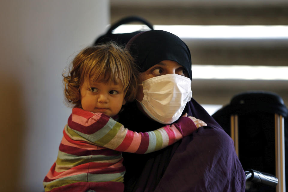 """An Albanian woman carries a child as she waits at the Rafik Hariri International Airport, during an operation to take them back home to Albania from al-Hol, northern Syria, in Beirut, Lebanon, Tuesday, Oct. 27, 2020. The repatriation of four children and a woman related to Albanian nationals who joined Islamic extremist groups in Syria """"is a great step"""" to be followed by more repatriations, Albania's prime minister said Tuesday in Beirut. (AP Photo/Bilal Hussein)"""