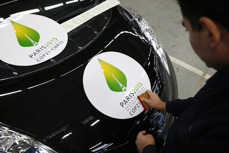 An employee applies a COP21 climate-summit sticker on an electric Renault/Nissan Leaf car on November 16, 2015, as France readies for the global conference