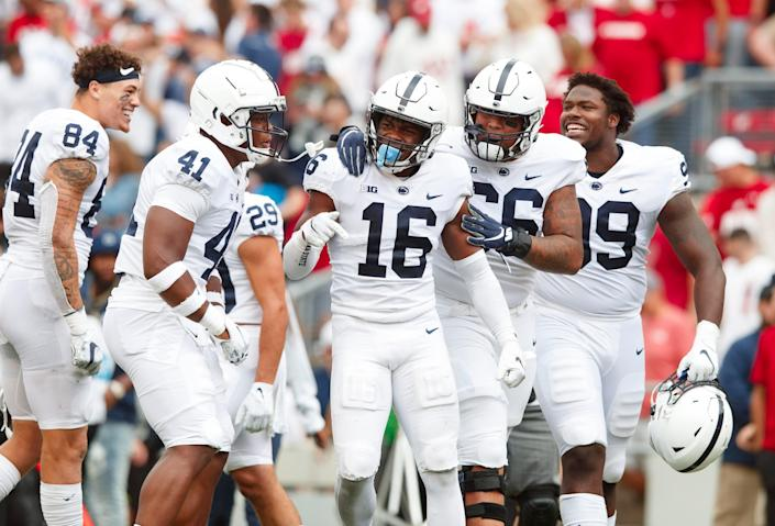 Penn State Nittany Lions safety Ji'Ayir Brown (16) is surrounded by teammates following the game against the Wisconsin Badgers at Camp Randall Stadium.