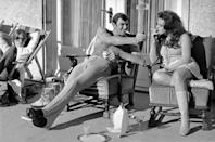 <p>George Lazenby offers co-star Helena Ronee a light, whilst filming 'On Her Majesty's Secret Service' in the Swiss Alps, 1969.</p>