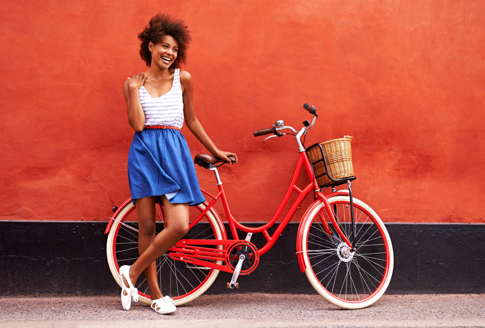 Young smiling woman standing in front of an orange wall with her bicycle