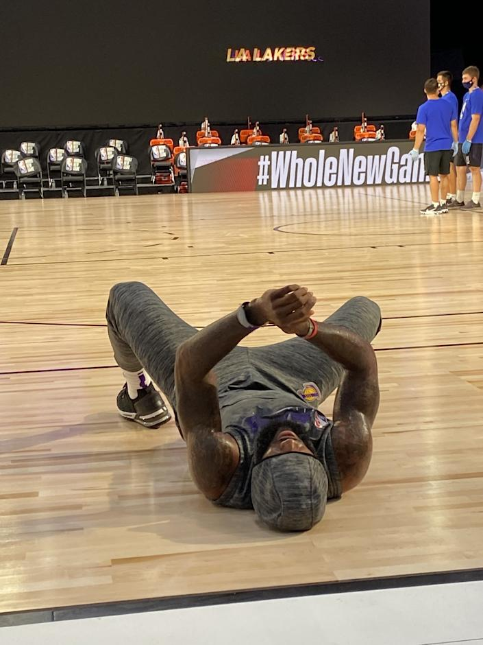 "Lakers star LeBron James, while wearing his MagicBand, stretches before a game in the NBA bubble in Orlando. <span class=""copyright"">(Tania Ganguli / Los Angeles Times)</span>"