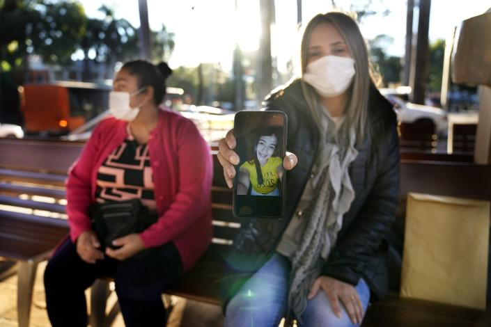 Lourdes Luna holds out her cellphone to show an undated selfie of her cousin Lady Vanessa Luna Villalba, as she sits with Lady's mother Juana Villalba at the entrance of the U.S. embassy where they are picking up their tourist visas in order to fly to the U.S., in Asuncion, Paraguay, Friday, July 2, 2021. Lady Luna, a nanny employed by the sister of Paraguay's first lady Silvana Lopez Moreira, was in the Champlain Towers South condominium when it collapsed in Surfside, Florida on June 24 and is still missing. (AP Photo/Jorge Saenz)