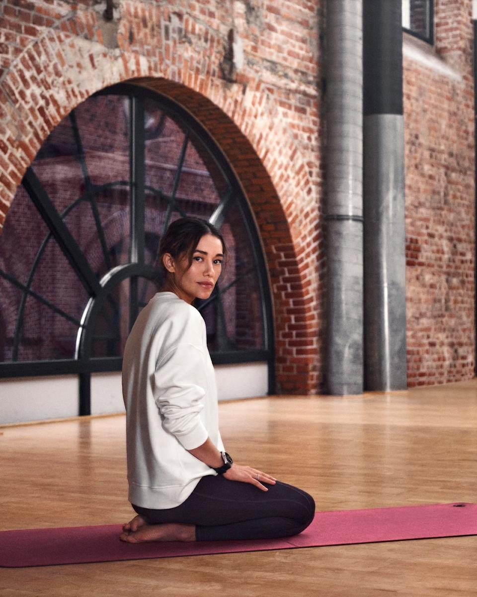 <p>Montblanc Summit Lite. A woman wearing the Summit Lite on her left wrist sits on a yoga mat with her legs bent below her in a loft.</p>