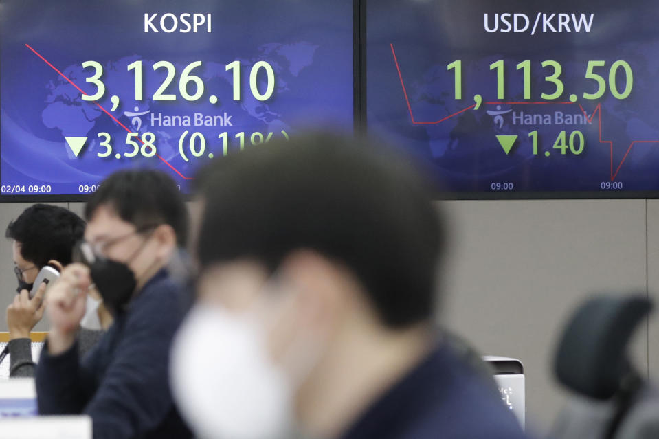 Currency traders watch computer monitors near screens showing the Korea Composite Stock Price Index (KOSPI), left, and the foreign exchange rate between U.S. dollar and South Korean won at the foreign exchange dealing room in Seoul, South Korea, Thursday, Feb. 4, 2021. Asian shares mostly fell Thursday as caution set in over company earnings reports, recent choppy trading in technology stocks and prospects for more economic stimulus for a world battling a pandemic. (AP Photo/Lee Jin-man)
