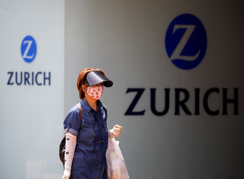 A woman wearing a protective face mask walks past in front of a office building of the Japanese unit of Zurich Insurance Group during a nationwide state of emergency in Tokyo, as the spread of the coronavirus disease (COVID-19) continues in Japan