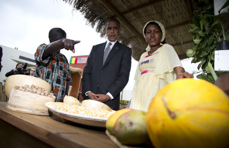 U.S. President Barack Obama, center, takes a tour during a food security expo on Friday, June 28, 2013, in Dakar, Senegal. Obama met with farmers, innovators, and entrepreneurs whose new methods and technologies are improving the lives of smallholder farmers throughout West Africa. (AP Photo/Evan Vucci)