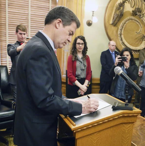 After announcing he would veto the tax bill sent to him by the legislature, Gov. Sam Brownback officially signs the veto, in his ceremonial office Wednesday, Feb. 22, 2017, as he stands in front of the assembled media. (Thad Allton /The Topeka Capital-Journal via AP)