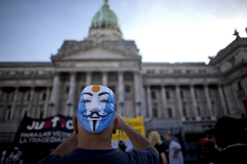 A man wearing a mask on his head takes a picture of the Congress as he protests the comprehensive judicial reform proposed by President Cristina Fernandez in Buenos Aires, Argentina, Wednesday, April 24, 2013. Lawmakers have started Wednesday to address three bills of the controversial judicial system, two of them regarding the regulation of injunctions against the state and the creation of three new Cassation Courts. (AP Photo/Natacha Pisarenko)
