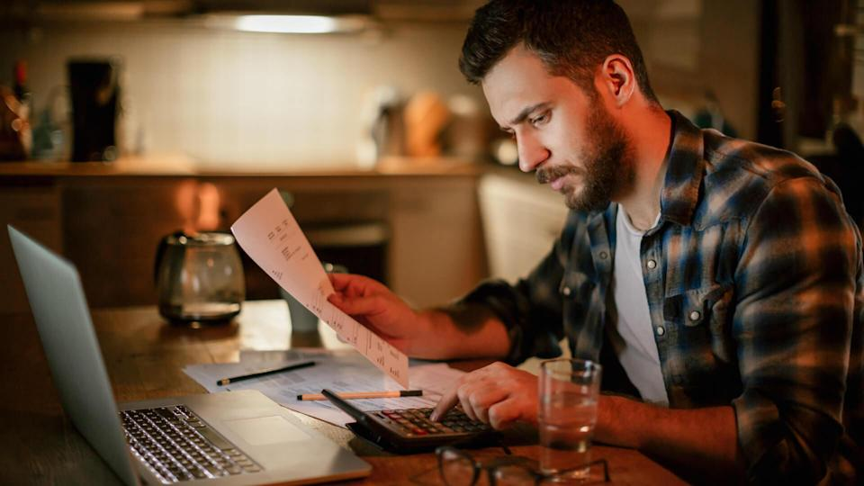 Photo of a stressed man going trough his financials problems,he is sitting in kitchen late at night checking and paying bills.