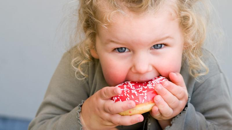 Young girl aged 2 to 3 years eating donut with pink icing.