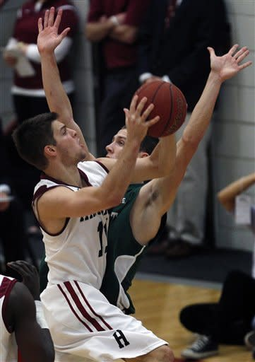 Harvard guard Oliver McNally, left, drives to the basket against Dartmouth forward Gabas Maldunas, rear, in the second half during an NCAA college basketball game in Cambridge, Mass., Saturday Jan. 7, 2012. McNally had 17 points in Harvard's 63-47 win. (AP Photo/Charles Krupa)