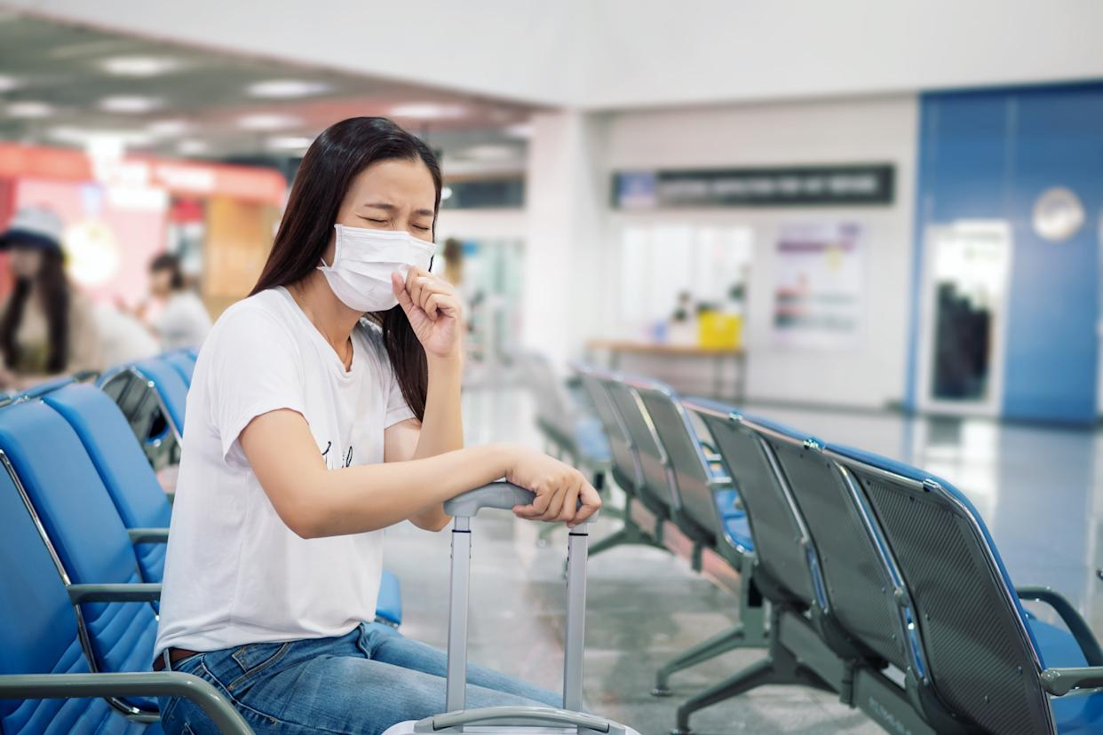 Asian tourist feeling sick, coughing ,wearing mask to prevent during travel time at the airport terminal for protect from the new Coronavirus 2019 infection outbreak situation