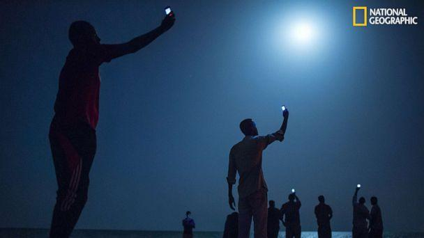 PHOTO: Impoverished African migrants crowd the night shore of Djibouti city, trying to capture inexpensive cell signals from neighboring Somalia—a tenuous link to relatives abroad. (John Stanmeyer/National Geographic)