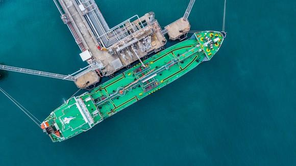 An aerial view of an LNG carrier loading up at a port.