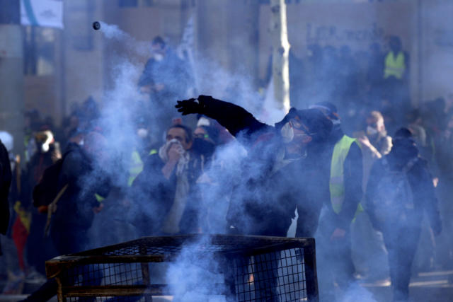 Protesters clash with riot police during a yellow vests demonstration Saturday, March 16, 2019 in Paris. Paris police say more than 100 people have been arrested amid rioting in the French capital by yellow vest protesters and clashes with police. They set life-threatening fires, smashed up luxury stores and clashed with police firing tear gas and water cannon (AP Photo/Christophe Ena)