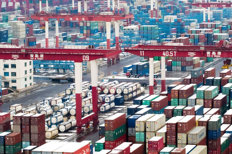 Containers and trucks are seen following a snowfall at the port of Qingdao