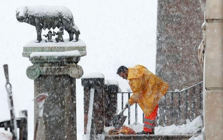 A worker removes the snow at the Campidoglio palace during an heavy snowfall in Rome, Italy February 26, 2018. REUTERS/Remo Casilli
