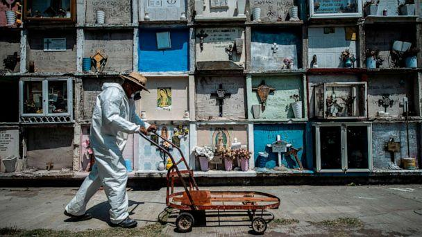 PHOTO: In this file photo taken on May 18, 2020 a Nezahualcoyotl municipal pantheon worker pushes a cart passing by graves in Ciudad Nezahualcoyotl, Mexico State, Mexico, amid the new coronavirus pandemic. (Pedro Pardo/AFP via Getty Images)