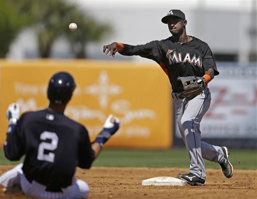 Miami Marlins shortstop Adeiny Hechavarria, right, puts out New York Yankees Derek Jeter (2), who avoids a hard slide as Yankees Ichiro Suzuki (not shown) hit into a third-inning fielder's choice in a spring training baseball game in Tampa, Fla., Friday, March 15, 2013. (AP Photo/Kathy Willens)