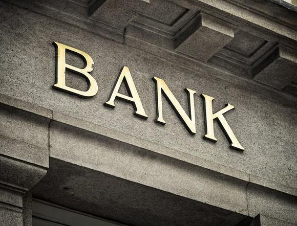 "Letters spelling out ""bank"" on a stone building facade."