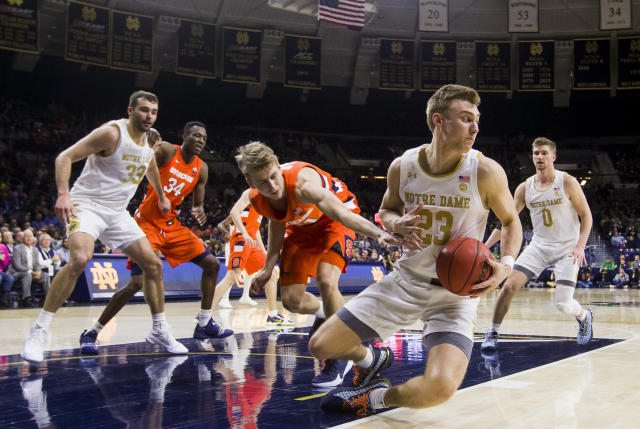 Notre Dame's Dane Goodwin (23) grabs a loose ball in front of Syracuse's Marek Dolezaj during the second half of an NCAA college basketball game Wednesday, Jan. 22, 2020, in South Bend, Ind. Syracuse won 84-82. (AP Photo/Robert Franklin)
