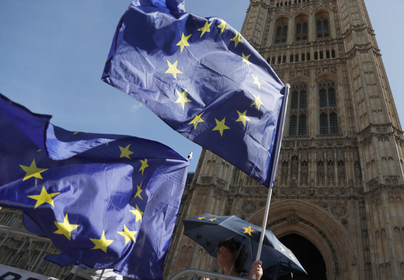 Anti Brexit protestors wave their flags opposite Parliament in London, Thursday, Aug. 29, 2019. Political opposition to Prime Minister Boris Johnson's move to suspend Parliament is crystalizing, with protests around Britain and a petition to block the move gaining more than 1 million signatures.(AP Photo/Frank Augstein)