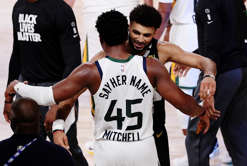 Jamal Murray and Donovan Mitchell embraced after their historic playoff duel. (Mike Ehrmann/Getty Images)