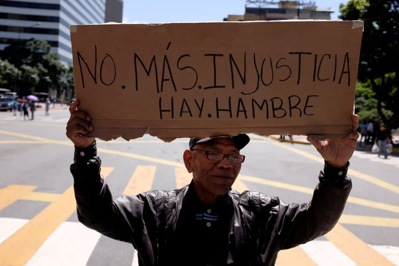 """FILE PHOTO: A man holds a placard that reads """"No more injustice. There is hunger"""" during a retirees protest for their pension in Caracas"""