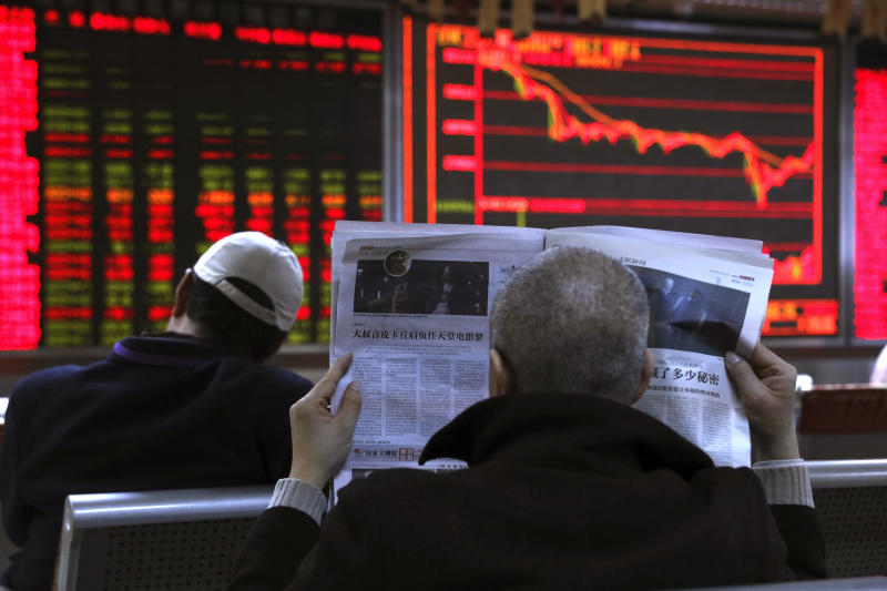 An investor reads the newspaper at a brokerage in Beijing, China, Friday, Nov. 16, 2018. Shares were mixed in early trading in Asia on Friday on revived concerns over the prospects for a breakthrough in trade tensions between the U.S. and China. (AP Photo/Ng Han Guan)