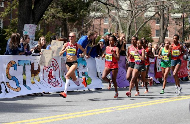 Shalane Flanagan leads Buzunesh Deba, of Ethiopia, and Mare Dibaba, of Ethiopia, and the elite pack past the cheering Wellesley College students during the 118th Boston Marathon Monday, April 21, 2014 in Wellesley. (AP Photo/Mary Schwalm)