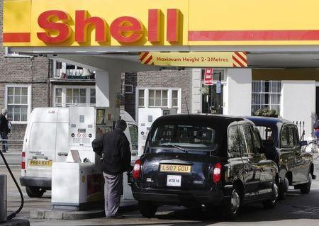 A taxi driver re-fuels his taxi at a Shell petrol station in London