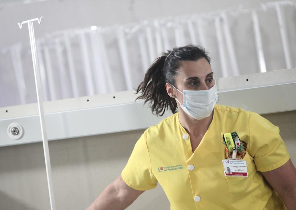 MADRID, SPAIN - MARCH 30: A nurse is seen carrying material while installing a campaign hospital that will admit 50 beds, helping to alleviate pressure on the Hospital of Fuenlabrada in the fight against coronavirus and will directly connect to the Oncology section on March 30, 2020 in Madrid, Spain. (Photo by Eduardo Parra/Europa Press via Getty Images)