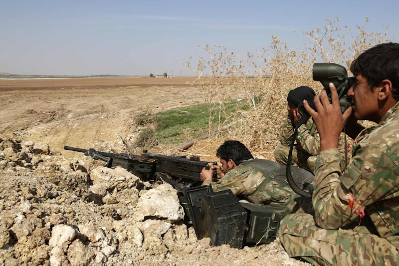 Turkish-backed Syrian rebels take aim towards the border town of Ras al-Ain on Oct. 12, 2019, as Turkey and it's allies continued their assault on Kurdish-held border towns in northeastern Syria.